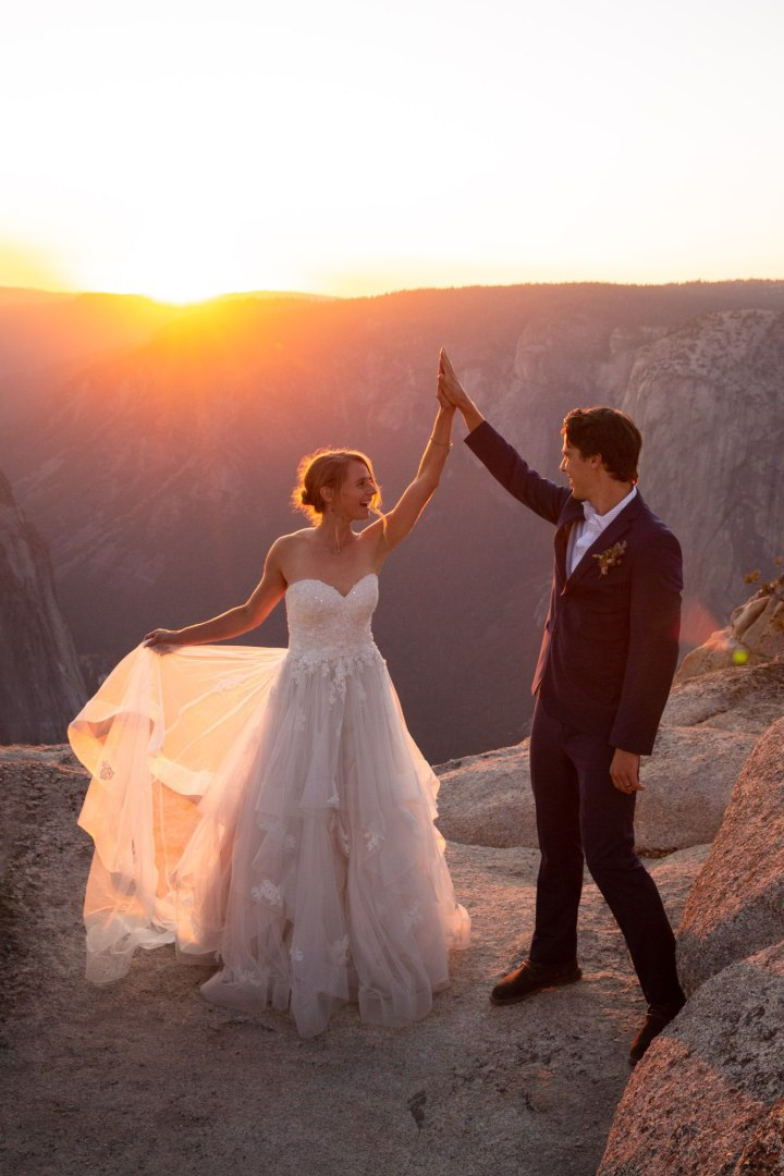 Couple high-five and look at each other while bride holds out her dress to catch the sunlight