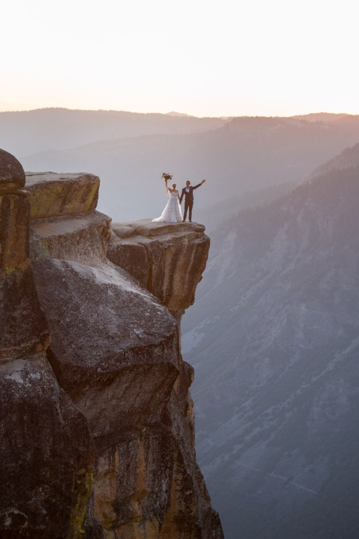 Couple stand at Taft Point with arms raised in the air.