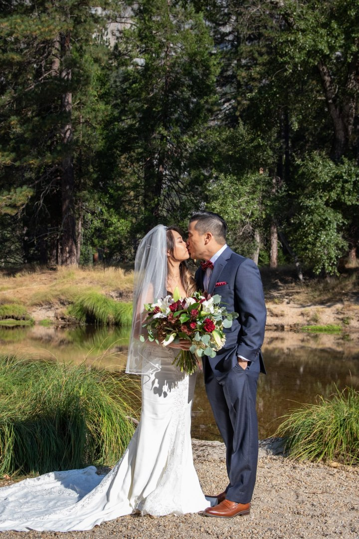 First kiss after a beautiful Yosemite elopement on the river.