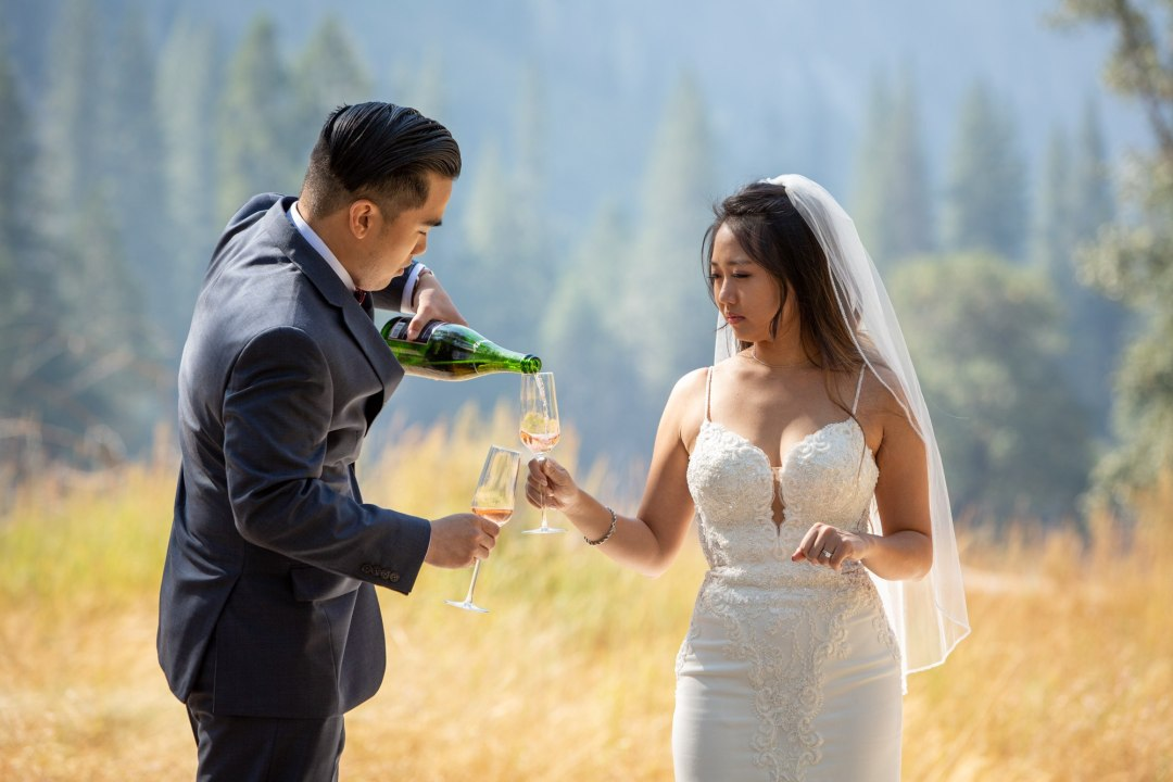 Groom pours champagne for his wife for a toast after their intimate wedding.