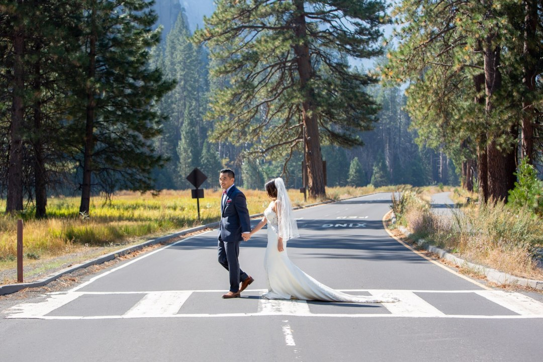 Groom leads his new wife to the car to head up to Glacier Point after the Yosemite Valley elopement.