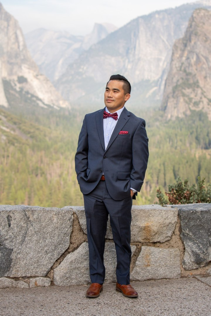 Handsome groom wearing a dark navy suit and red bow tie for his adventure elopement.
