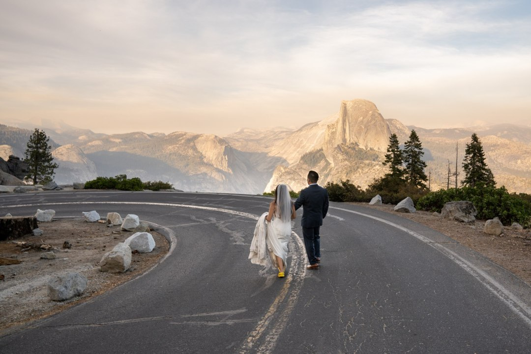 Newlyweds run down the road towards Half Dome for their Glacier Point intimate wedding!