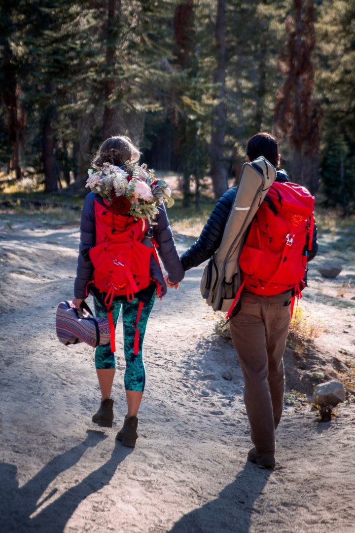 A couple walk hand-in-hand down a wooded trail with red backpacks, one with a beautiful wedding bouquet inside.