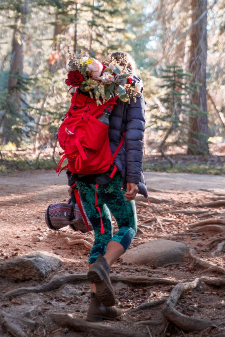 Bride to be walks on a wooded trail, wearing bright colorful pants and hiking boots. Her red backpack has her flowers in it.