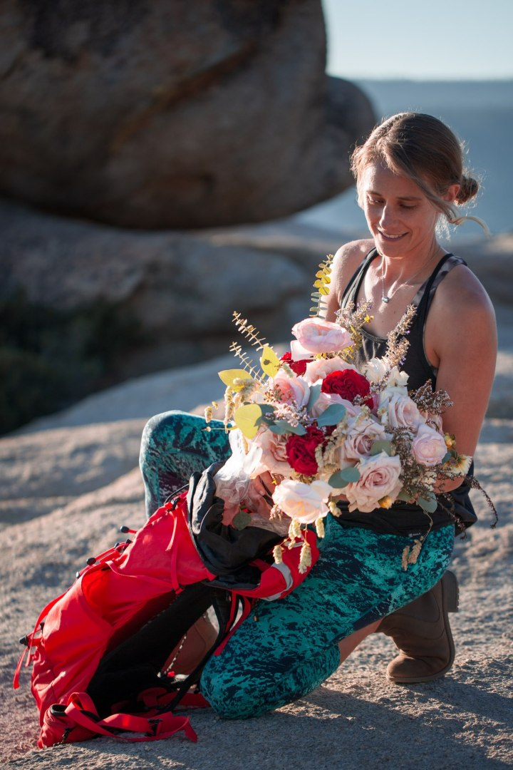 Woman takes bridal bouquet out of her red backpack