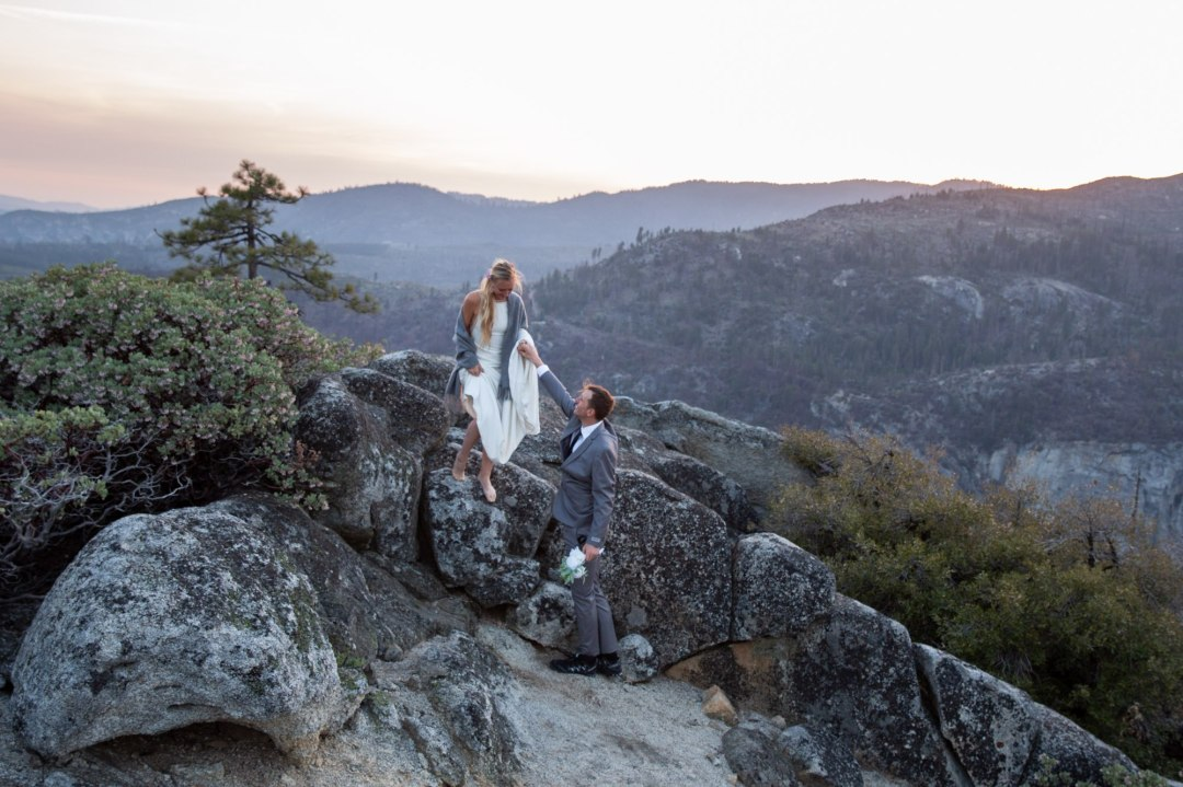Bride and groom standing arm in arm while looking out over the Yosemite Valley after their adventure elopement ceremony.