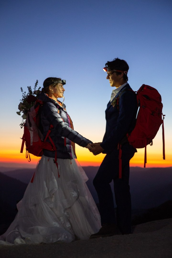 Couple wearing headlamps and red backpacks standing facing each other holding hands