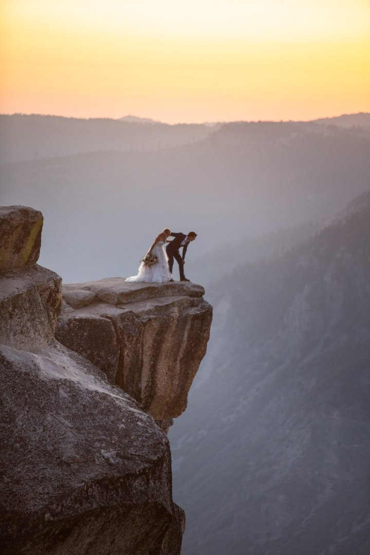Bride and Groom peering over the edge on Taft Point Yosemite,  during a killer sunset adventure elopement.