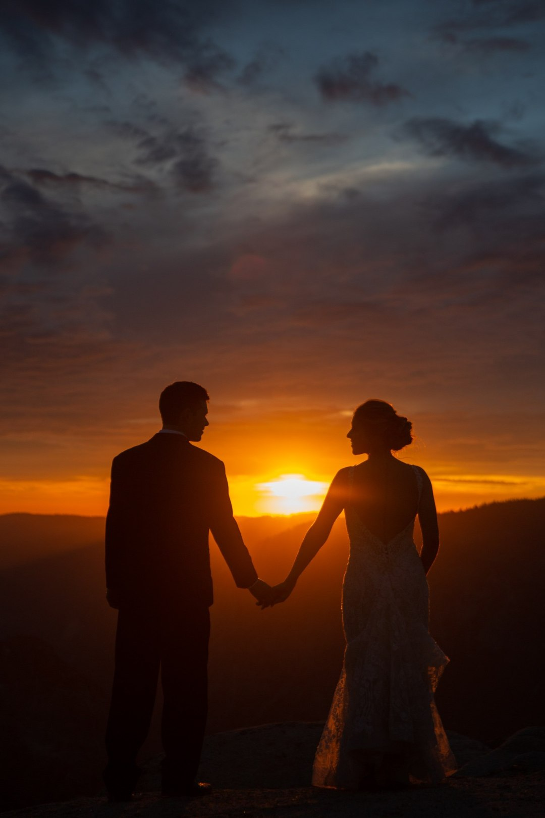 Bride and groom hold hands and look into the last light of the setting sun from Taft point. Another perfect Yosemite wedding is a wrap!