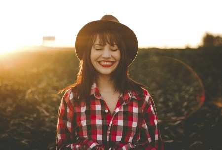 woman smiling in front of a sunset