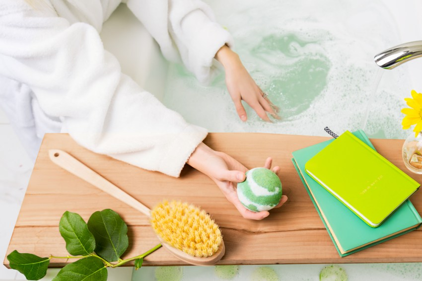 photo of woman filling her tub and adding a scentsy bath bomb