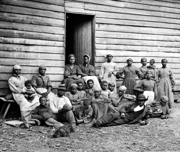 A large group of slaves of all ages sitting outside a plantation hut