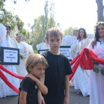 Two young children stare at the camera, surrounded by Climate Angels in white. by Takver at mass demonstration in Melbourne CC BY-SA 2.0
