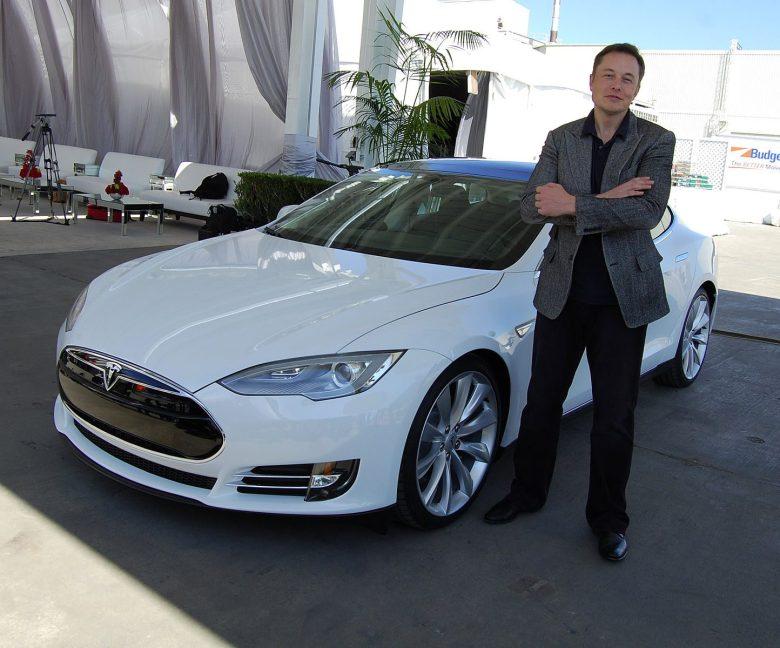 Elon Musk posing in front of a Tesla car.