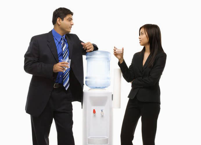 Image of two business people at a water cooler