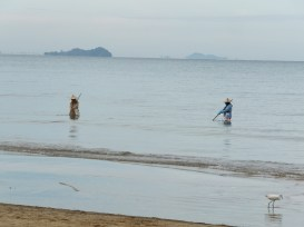 Locals cleaning up the beach at Tg. Aru Beach in the waters of South China Sea