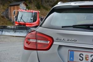 Der Mercedes-Benz GLA auf der Heimalm neben einem Pistenbully