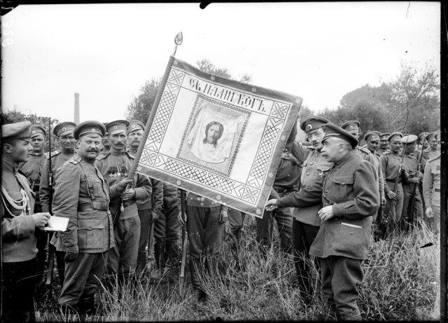 Au camp Mirabeau près de Marseille, les hommes du premier régiment de la première brigade russe posent aux côtés de leur drapeau, orné du visage du Christ et frappé de la devise tirée d'Isaïe