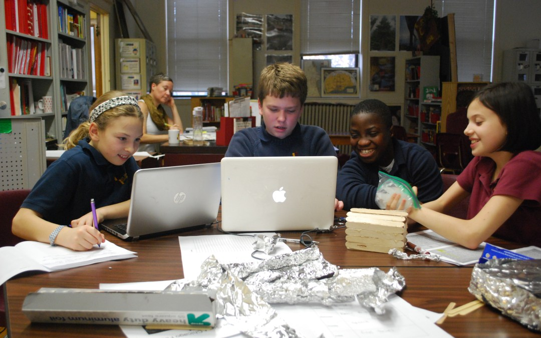 Middle school students work in a group on laptops.