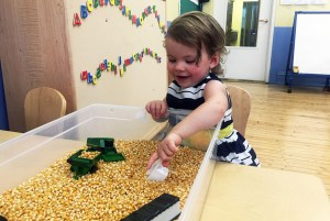 A child playing in a sensory table during learning lab.