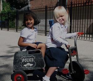 preschool students riding bikes during recess.