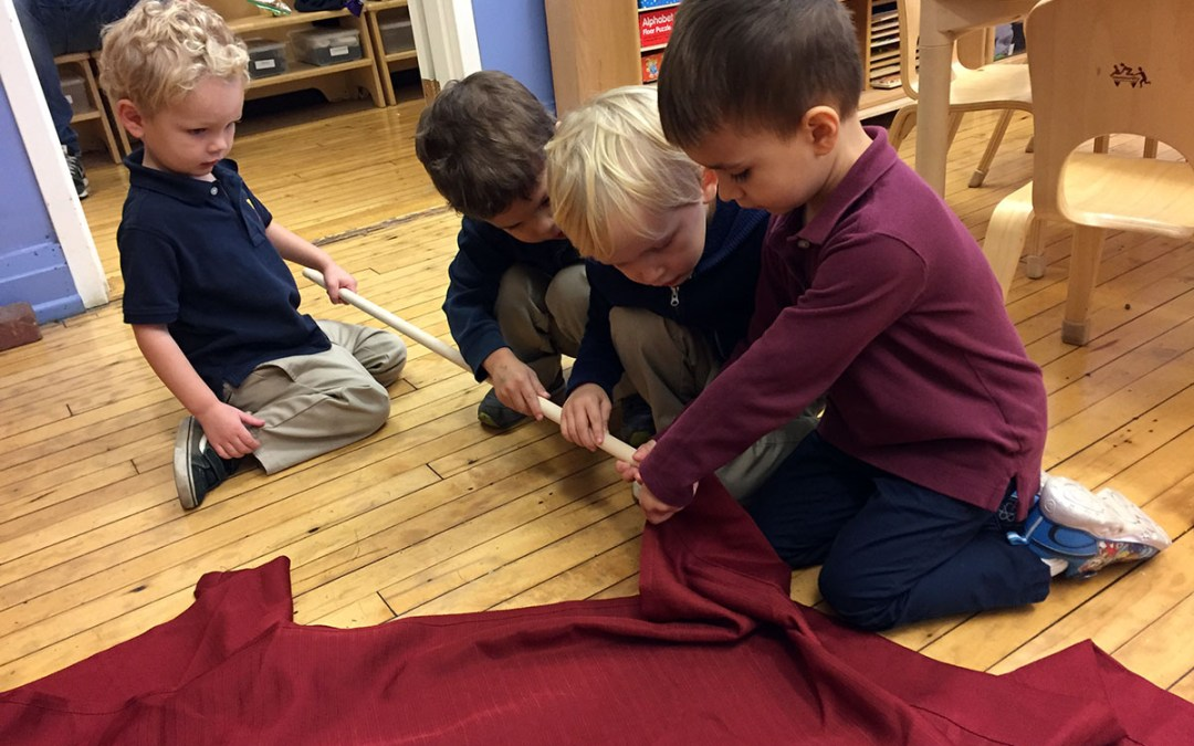 Early childhood students working together to put up a curtain.