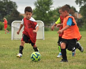 Youngsters go after the ball in a friendly scrimmage near the end of their day at Victory Soccer camp in August 2014.