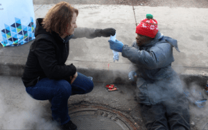 Cook gifts a pair of socks to a homeless man. Socks are one of the most needed items.