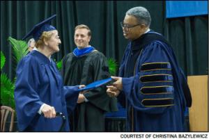 Violet Janowski shakes President Jeffress' hand at graduation