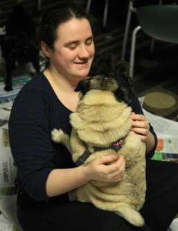 Marissa Petitpas hugs one of the many pugs to choose from.