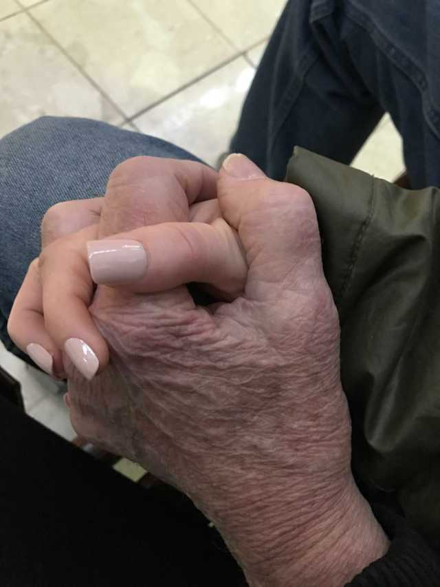 A young woman's hand clasps an aged, wrinkled hand.