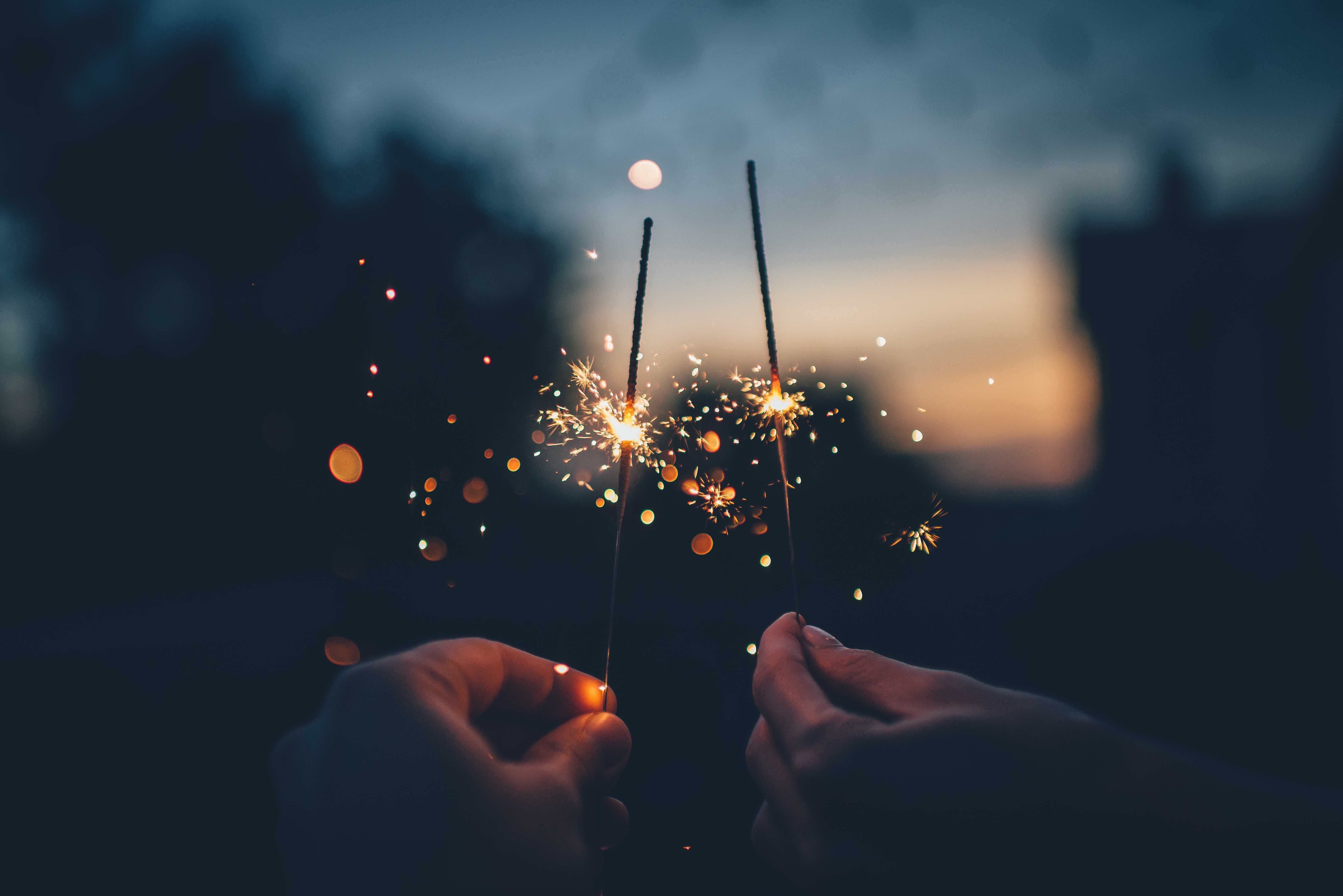 Two hands holding sparklers in twilight. (Image from Pixabay.com)