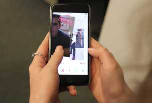 A woman's hands are shown holding a phone with a dating app open.