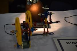 A small robot stood turning gears with a handle.