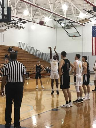 Kemon Bassett, #12, is making his shot at a free-throw, as Ocelots and Lumberjacks stand around him.