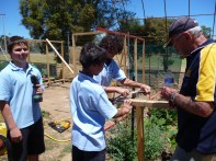 students attaching stirrup brackets to the posts