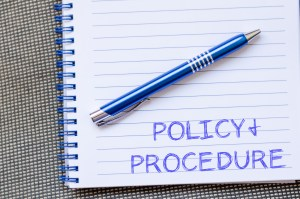 Policy and procedure text concept write on notebook with pen