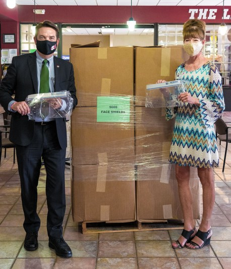 Lisa Winters, Director of Marketing and Community Relations for Peterson Health, presents Dr. Charlie McCormick, President of Schreiner University, with a donation of 5000 new, reusable face shields.