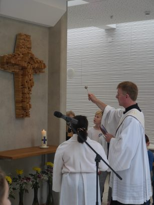 Segnung des Kreuzes mit Weihwasser.