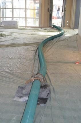 Eine grüne Schlange schlängelt sich durch den Erweiterungsbau. In ihr wird mit Hochdruck Kies aufs Dach befördert. Dies ist ziemlich laut!