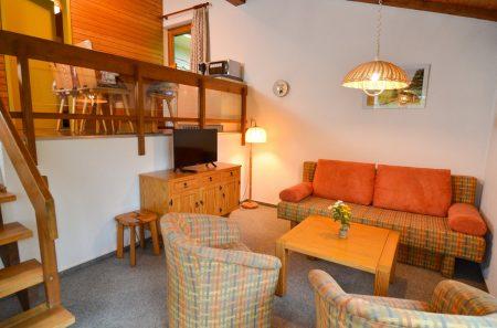 Wohnbereich mit zwei Sessel und Sofa, oben Galerie mit Essbereich und Küche