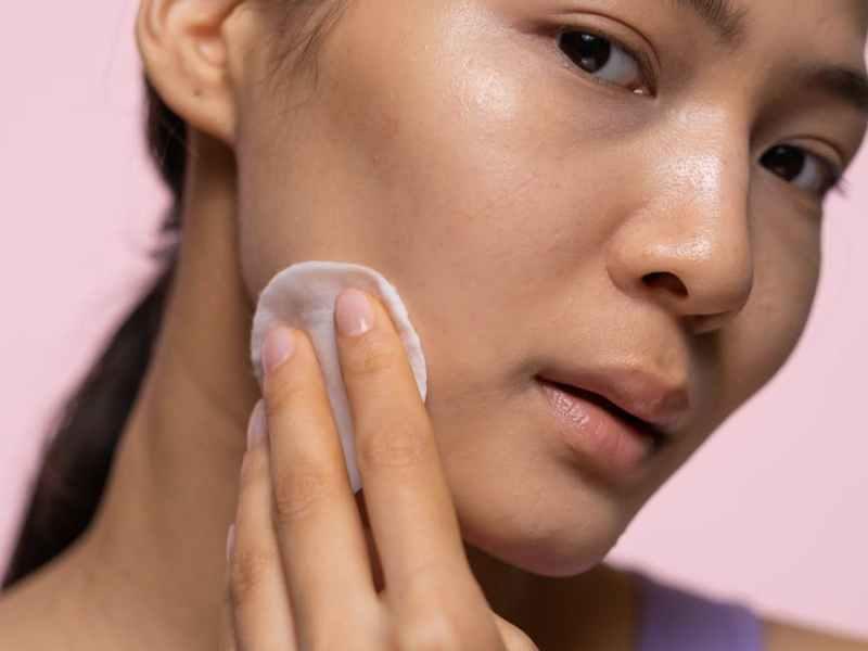 woman in purple tank top applying facial tonic
