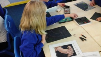 A pupil at Bishops Nympton Primary School making art inspired by Gosse's illustrations.