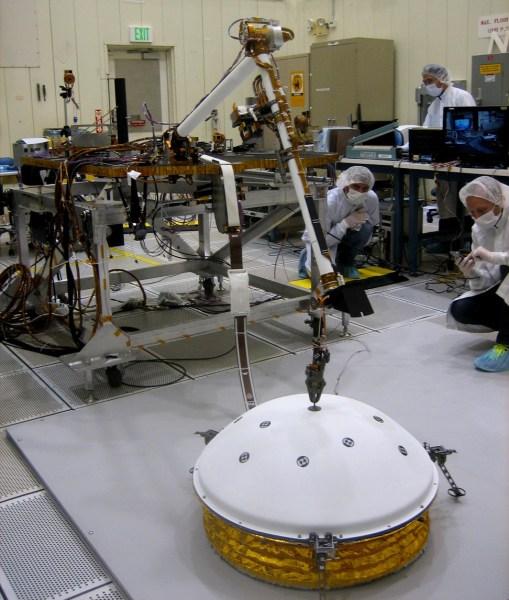 Bei einem Test am Jet Propulsion Labor setzt der Roboterarm IDA (Instrument Deployment Arm) das Seismometer SEIS ab. Bild: NASA/JPL-Caltech, gemeinfrei.