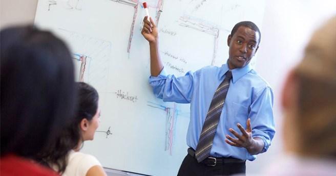Male teacher standing at a whiteboard teaching a class
