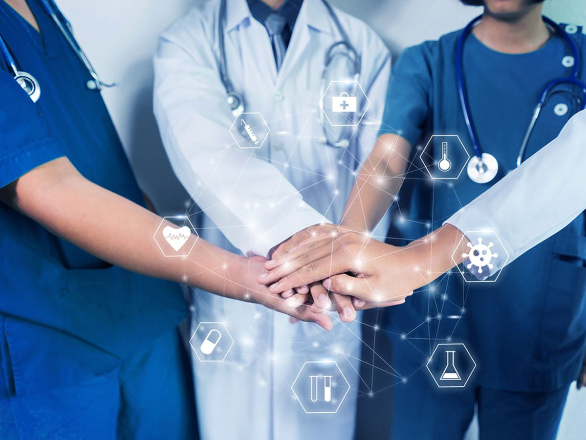 Medical and healthcare nurses and doctors working to together fighting pandemic of corona virus disease, standing around with hands on top each other forming strong bond, motivation and coordination