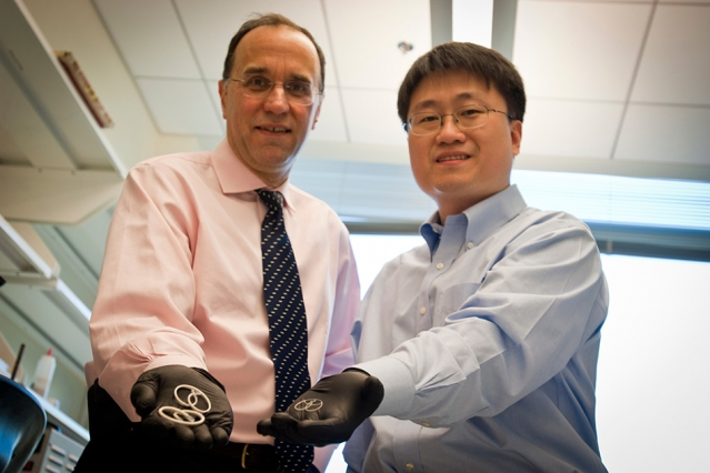 Professor Michael Cima (left) and alumnus Heejin Lee display early prototypes of the LiRIS devices. The pretzel-shaped silicone tubes can be inserted into the bladder, slowly releasing lidocaine over two weeks to treat interstitial cystitis.