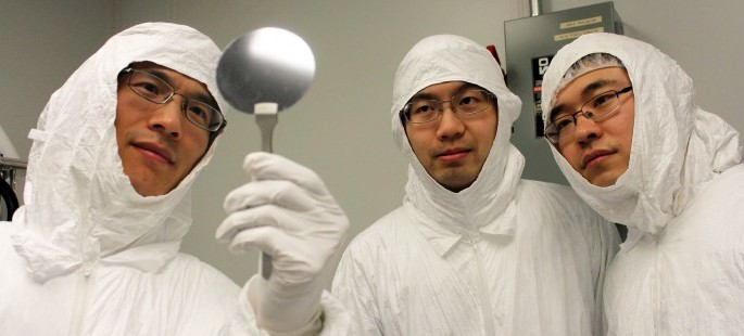 UMass Amherst Professor Qiangfei Xia and two students in clean suits view wafer