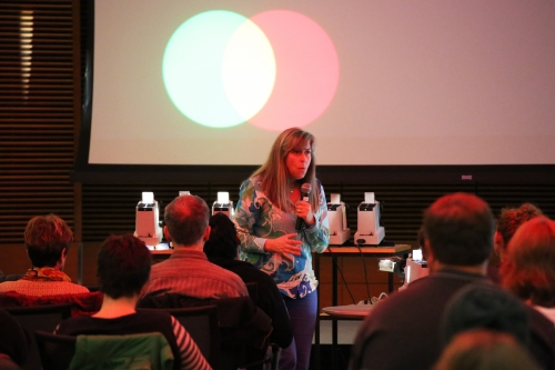 """Photo: Pupa Gilbert, a professor of physics at UW-Madison, presents the physics of color at the Nerd Nite event during the 2015 Wisconsin Science Festival. At the 2016 festival, Nerd Nite is a partner in the """"Science Storytellers Jam!"""" that aims to engage audiences in science through creative storytelling."""